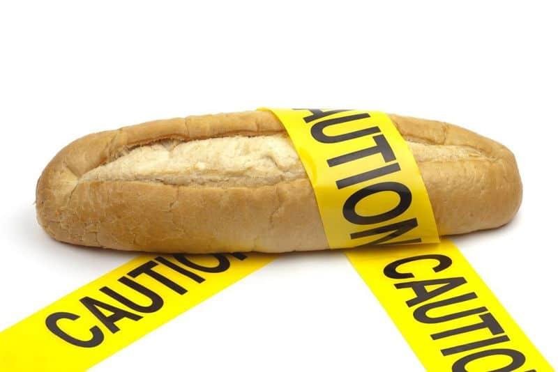"""Weizenbrot umwickelt mit Band, das die Aufschrift """"Caution"""" trägt."""